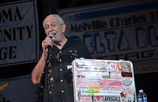 Charlie Musselwhite performing next to the  harmonica case he carries around the world publicizing I love Clarksdale